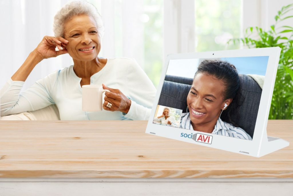 Black grandmother using the Sociavi C2M device to communicate with her granddaughter.